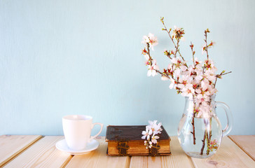old book, cup of coffee next to spring white flowers