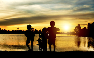 silhouette of a happy family of four people, baby, and child, and their dog in front of a sunsetting sky, with room four copy space or text