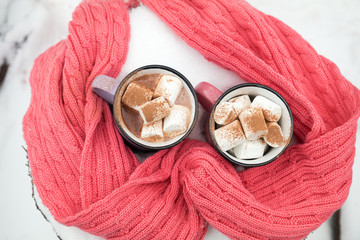 Hot chocolate with marshmallow in pink and violet two cups wrapped in a cozy winter pink scarf on the snow-covered table in the garden. Coloring and processing photo, small depth of field
