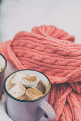 Hot chocolate with marshmallow in violet cup wrapped in a cozy winter pink scarf on the snow-covered table in the garden. Coloring and processing photo, selective focus, small depth of field