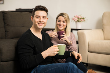 Young man drinking coffee with his girlfriend