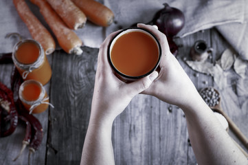 Iron mug with carrot juice in female hands