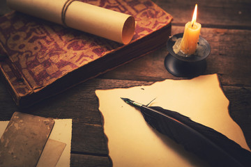 vintage feather with paper and old book on table in light of can