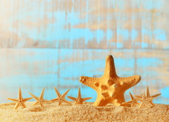 Sea sand with starfish on wooden background.
