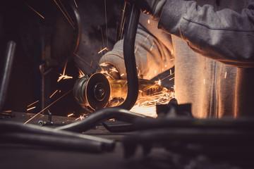 Metal grinding steel pipe loops with flash of hot sparks