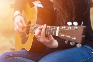 Woman's hands playing acoustic guitar, close up and select focus