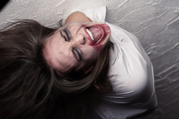 screaming crazy woman with flying hair in straitjacket