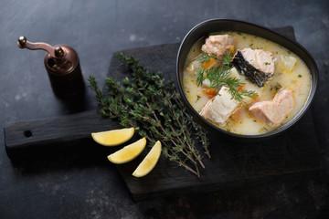 Bowl of salmon soup on a dark wooden chopping board, studio shot