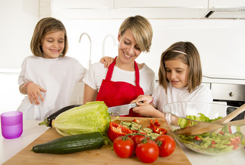 young mother in cook apron and sweet beautiful twin daughters cooking preparing together salad