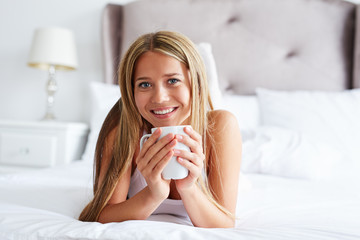 Smiling woman with cup of coffee or tea