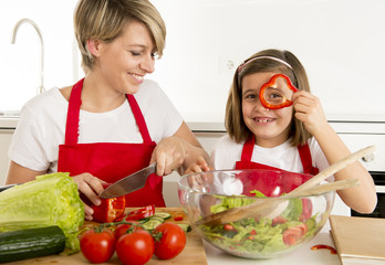 mother and little daughter cooking together with cook apron preparing salad at home kitchen