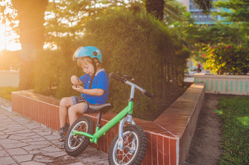 Active blond kid boy driving bicycle in the park near the sea. Toddler child dreaming and having fun on warm summer day. outdoors games for children