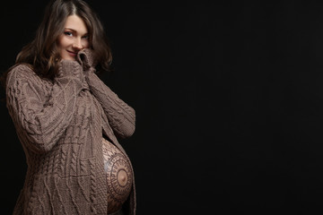 Pregnant woman posing with flower ornament on her belly, on black background.