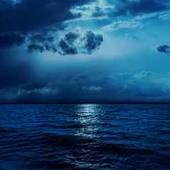 dark clouds in night with moonlights over water