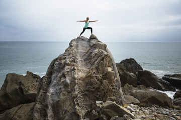 Woman practicing worrier 2 pose on rocks by sea