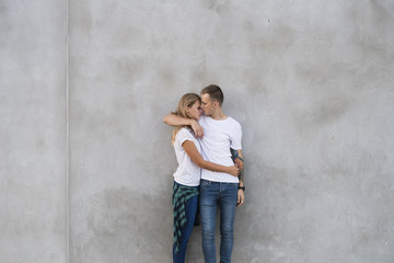 Romantic couple embracing while standing against gray wall