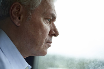 Thoughtful man looking through window while standing at home