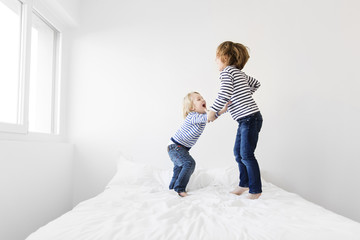 Happy siblings jumping on bed against wall at home