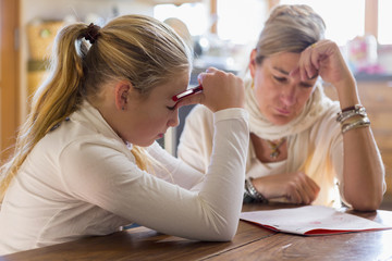 Mother assisting daughter in studying at home