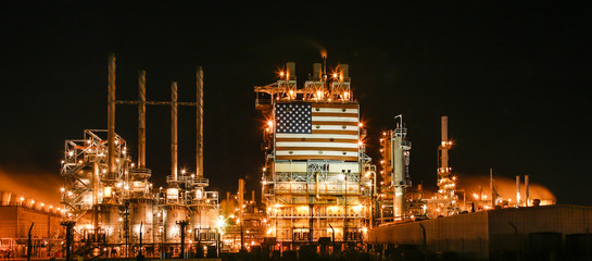 American flag on illuminated oil refinery against sky at night