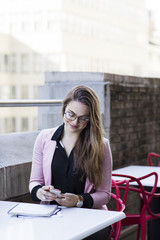 Businesswoman using mobile phone while sitting in balcony