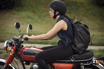 Side view of woman riding motorcycle on road