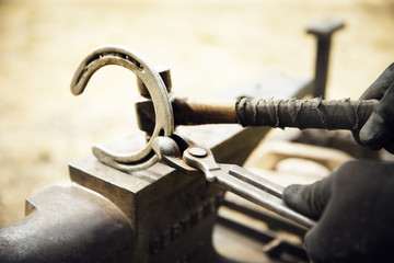 Cropped of farrier making horseshoe on anvil