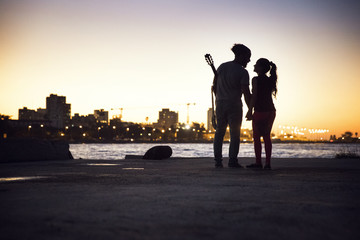 Silhouette couple standing at lakeshore against clear sky during sunset