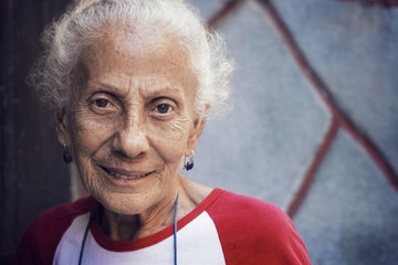 Portrait of a smiling senior woman standing against wall