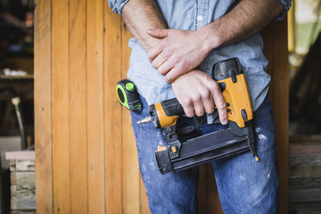 Midsection of craftsperson holding nail gun while standing at workshop