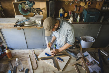 High angle view of artist making wooden art at workbench in workshop