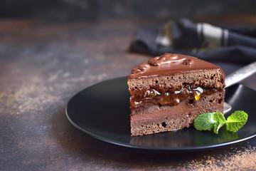 Piece of chocolate Sacher torte on a black plate .