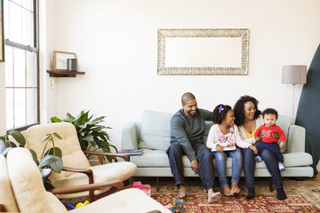 Happy family with picture book looking at baby boy while sitting on sofa