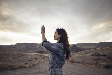 Woman photographing mountain while standing on field