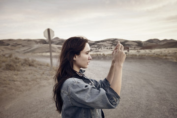 Woman photographing while standing on field against sky
