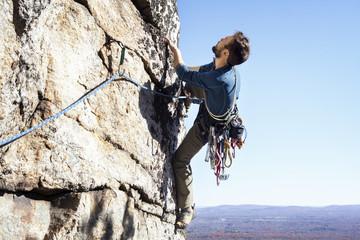 Man rock climbing against clear sky