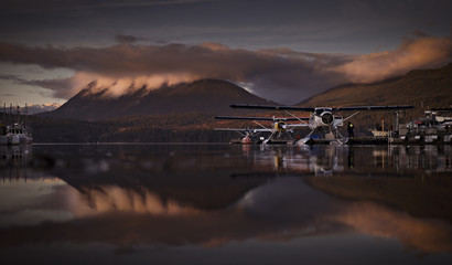 Biplanes parked in lake against mountain during sunset