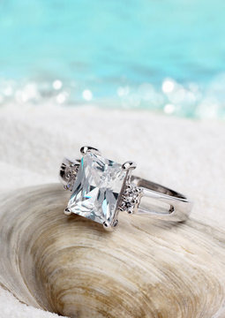 Jewelry ring with clean diamond on sand beach background, soft f