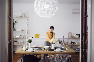 Woman arranging flowers at dinning table in home