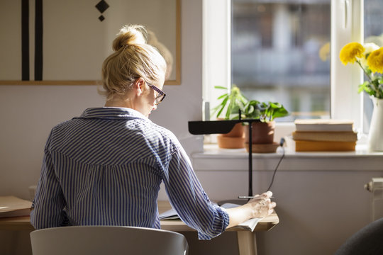 Rear view of woman writing while sitting at table