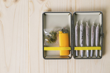 Overhead view of marijuana joints with cigarette lighter in container on table