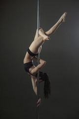 Woman exercising on pole against gray background