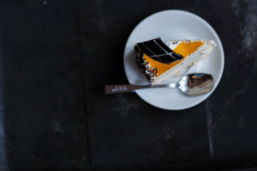 piece of cake on a white saucer on a black background copyspace