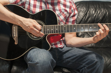 Man playing music on an acoustic guitar on a couch
