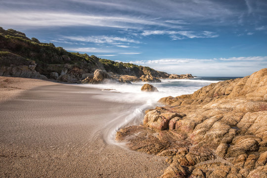 Waves wash onto a small sandy cove near Calvi in Corsica