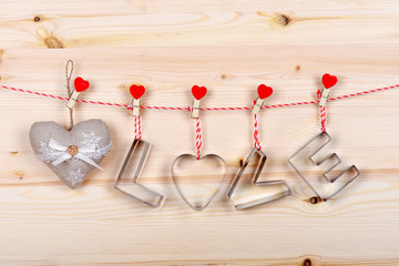 Silver text Love and heart for Happy Valentine's Day celebration on a pine wooden background