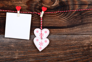 Two hearts and a blank sheet of paper on a beautiful old wooden background as love concept for valentines day