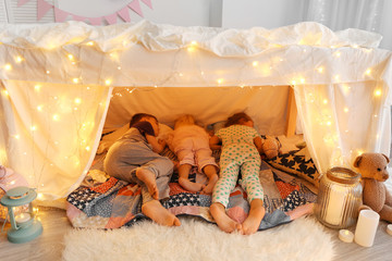 Cute little children sleeping in hovel at home Wall mural