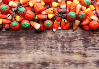 Colorful Halloween candies on wooden background