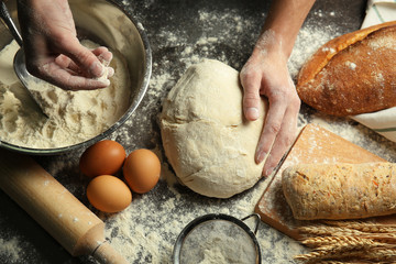 Male hands forming loaf of bread. Kitchenware and ingredients on sprinkled with flour table, closeup